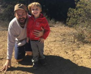 English professor Adam Bessie hiking with his son Sol