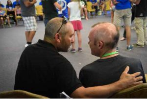 Two dads enjoying a conversation at camp