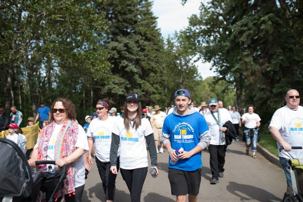 A brain tumour survivor, recognizable by his blue shirt, walks to end brain tumours in Edmonton, Alberta in May 2016